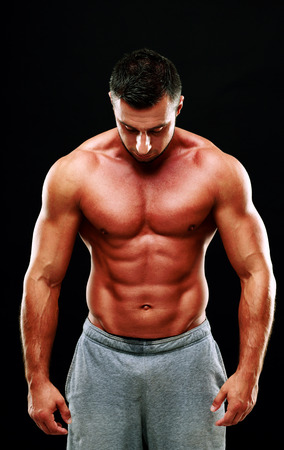 Portrait of a muscular man isolated on a black background photo