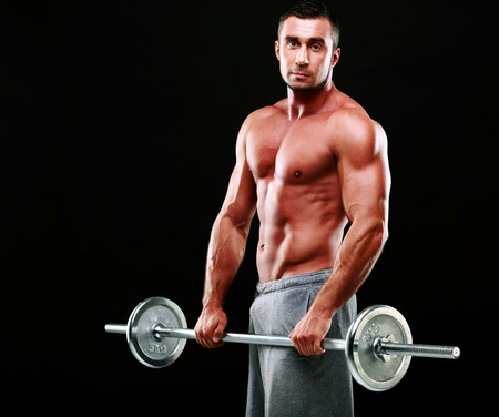 Muscular man standing with barbell over black background photo