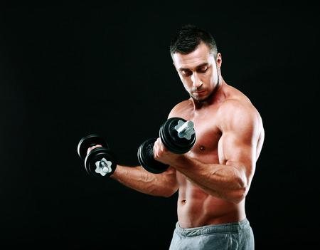 man working out: Hermoso hombre musculoso que se resuelve con pesas sobre fondo negro