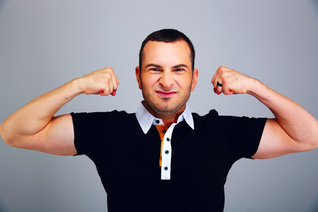 Man in casual cloth showing his biceps on gray background