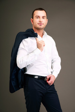 socialize: Handsome businessman holding his jacket over shoulder on gray background