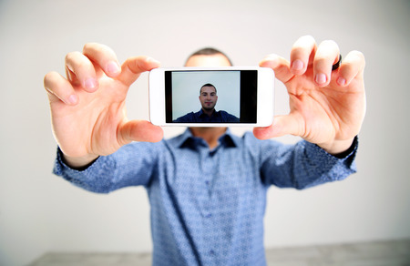profile picture: Portrait of a man taking selfie. Focus on smartphone Stock Photo