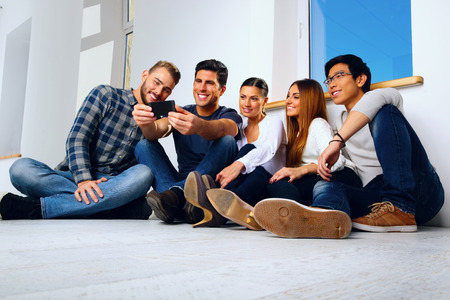 Portrait of a happy friends sitting on the floor and looking at smartphone photo