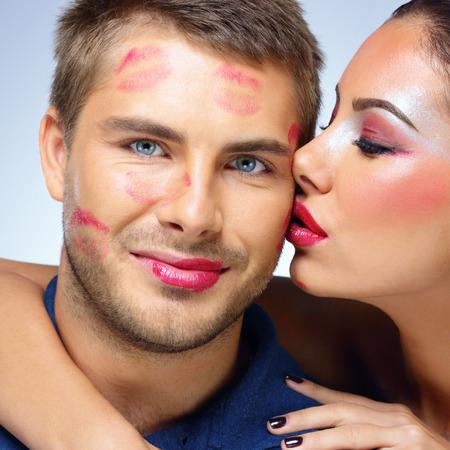 besos apasionados: Mujer atractiva que besa al hombre feliz sobre fondo azul Foto de archivo