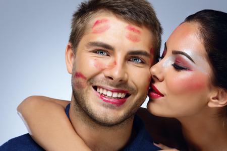 besos apasionados: Hermosa mujer besa al hombre feliz sobre fondo azul Foto de archivo