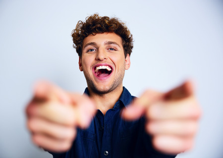 rude: Portrait of a laughing man pointing at you Stock Photo