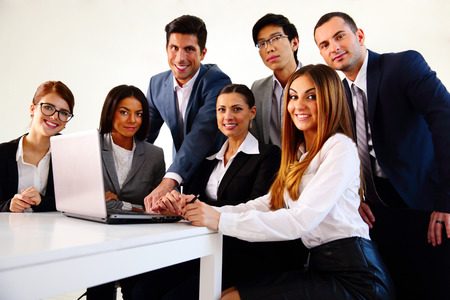 Happy businesspeople working on the laptop together photo