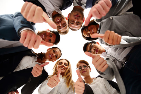 Group of business people standing in circle, with thumbs up photo