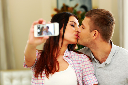Young couple kissing and making selfie photo on smarphone photo
