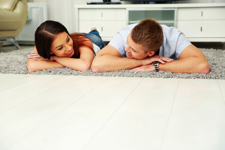 Happy couple relaxing on the floor at home photo
