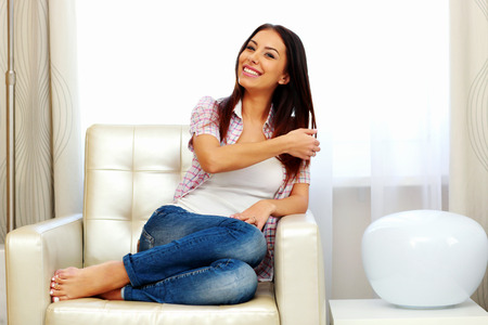 toothe: Smiling woman sitting on the sofa at home