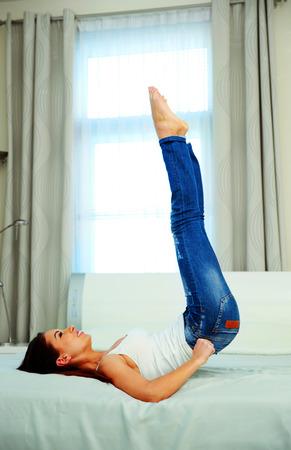 in jeans: Mujer hermosa joven que miente en la cama y tirando de los pantalones vaqueros