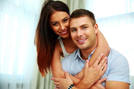 personas abrazadas: Sonriente joven pareja abrazándose en casa