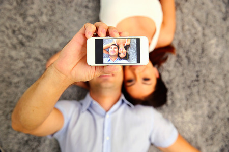 Couple lying on the floor and making selfie photo on smartphone. Focus on smartphone photo