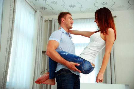 Man holding wife on the hands at home photo
