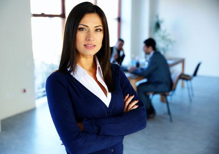 ejecutivo en oficina: Hermosa mujer de pie con los brazos cruzados con los colegas en el fondo Foto de archivo