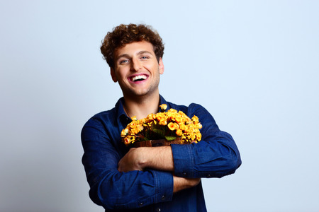 Happy man hugging bucket with flowers photo