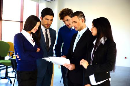 personas leyendo: La gente de negocios la lectura de un documento juntos en la oficina