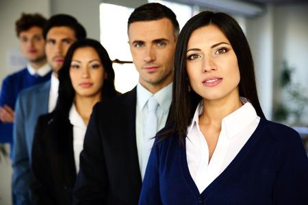 Groep van mensen uit het bedrijfsleven staan opgesteld in het kantoor Stockfoto