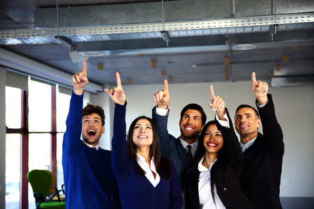 Group of cheerful business people pointing up photo