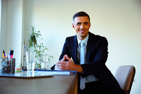 Happy businessman sitting at the table in office photo