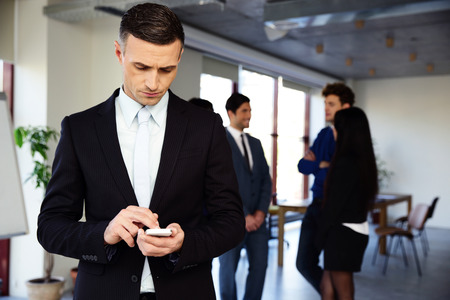Confident businessman using smartphone in front of a colleagues photo