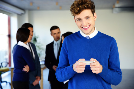 Happy businessman using smartphone in front of a colleagues photo