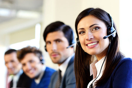 to phone calls: Smiling businesspeople in a call center office