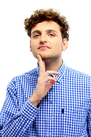 hait: Young casual man touching his chin over white background