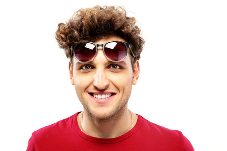 Happy fashion man with sunglasses over white background photo