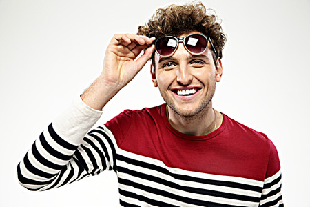 Happy fashion man with sunglasses over gray background photo