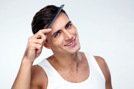 Happy man combing his hair over gray background Stock Photo