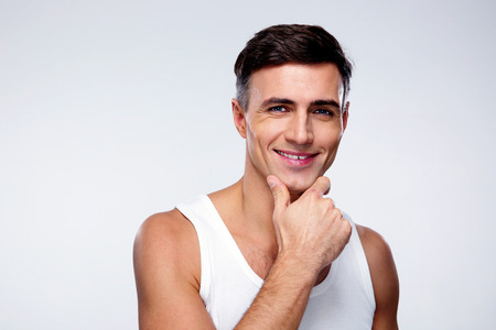 adolescent sexy: Portrait of a smiling young man over gray background
