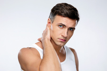Portrait d'un bel homme de toucher son cou sur fond gris Banque d'images - 34532336