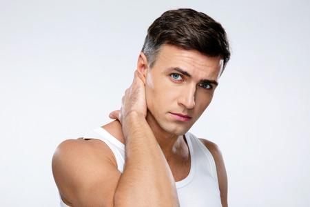 Ritratto di un uomo bello che tocca il collo su sfondo grigio