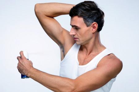Knappe man met behulp van deodorant over grijze achtergrond Stockfoto