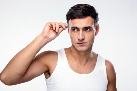 tweezing eyebrow: Handsome man removing eyebrow hairs with tweezing Stock Photo
