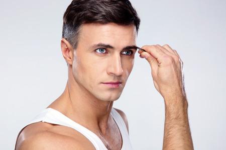 tweezing eyebrow: Man removing eyebrow hairs with tweezing Stock Photo