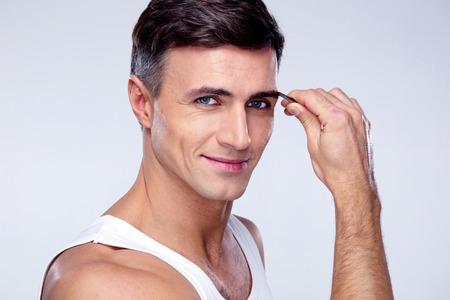 tweezing eyebrow: Happy man removing eyebrow hairs with tweezing Stock Photo