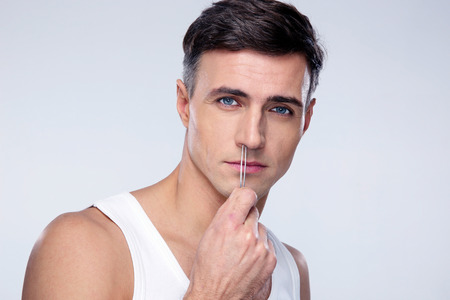 Man pucking nose hair with tweezers over gray background Stock Photo