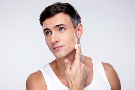 Knappe man brengen op crème lotion op gezicht