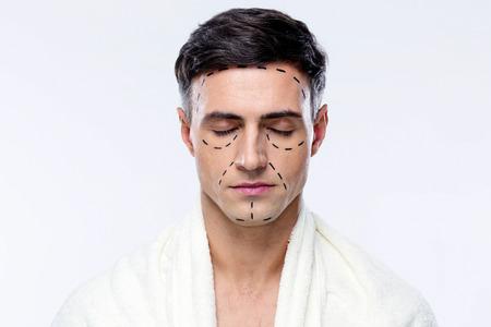 tratamiento facial: Hombre con los ojos cerrados y marcados con l�neas para la cirug�a pl�stica Foto de archivo