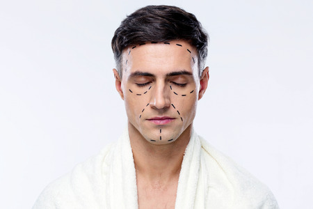 Man with closed eyes and marked with lines for plastic surgery