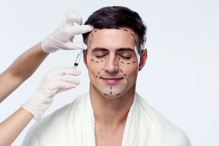 reg: Man with closed eyes at plastic surgery with syringe in his face Stock Photo
