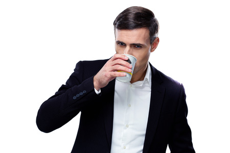 Handsome businessman drinking coffee over white background photo