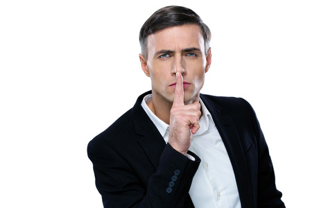 Businessman placing finger on lips saying shhh, be quiet! photo