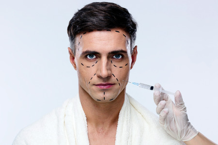 beauty treatment clinic: Man at plastic surgery with syringe in his face