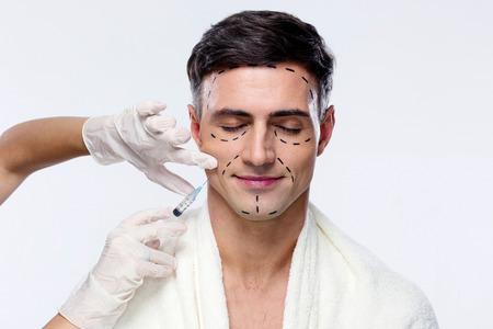 目を閉じて彼の顔に注射器で整形手術で男
