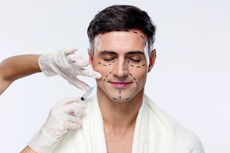 plastic glove: Man with closed eyes at plastic surgery with syringe in his face Stock Photo