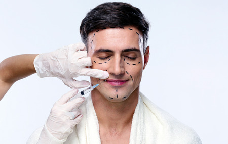 plastic glove: Handsome man with closed at plastic surgery with syringe in his face